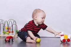 Entzückender Kleinkindjunge, der mit einer Spielzeugente auf dem grauen Boden spielt Lizenzfreie Stockfotos