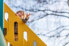 Entzückender Kleinkindjunge, der Spaß hat und auf playgroun im Freien schiebt Stockfotografie