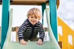 Entzückender Kleinkindjunge, der Spaß hat und auf playgroun im Freien schiebt Lizenzfreies Stockfoto