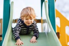 Entzückender Kleinkindjunge, der Spaß hat und auf playgroun im Freien schiebt Stockbilder