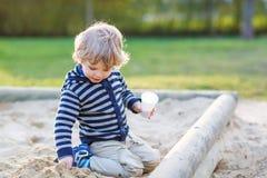 Entzückender Kleinkindjunge, der Spaß mit Sand auf Spielplatz im Freien hat Lizenzfreies Stockbild