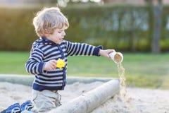 Entzückender Kleinkindjunge, der Spaß mit Sand auf Spielplatz im Freien hat Stockfotos
