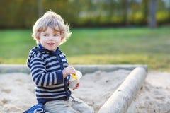 Entzückender Kleinkindjunge, der Spaß mit Sand auf Spielplatz im Freien hat Lizenzfreie Stockfotografie