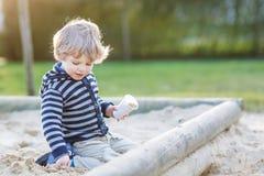 Entzückender Kleinkindjunge, der Spaß mit Sand auf Spielplatz im Freien hat Stockfoto