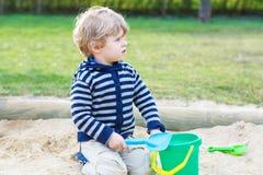 Entzückender Kleinkindjunge, der Spaß mit Sand auf Spielplatz im Freien hat Stockfotografie