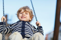 Entzückender Kleinkindjunge, der Spaßkettenschwingen auf playgroun im Freien hat Stockfotos