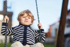 Entzückender Kleinkindjunge, der Spaßkettenschwingen auf playgroun im Freien hat Lizenzfreies Stockbild
