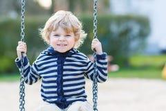 Entzückender Kleinkindjunge, der Spaßkettenschwingen auf playgroun im Freien hat Stockbilder