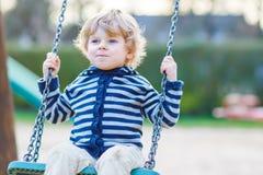 Entzückender Kleinkindjunge, der Spaßkettenschwingen auf playgroun im Freien hat Stockbild