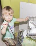 Entzückender lächelnder blonder Kleinkindjunge, der in der Küche nimmt Platten aus Geschirrspülmaschine heraus hilft Stockfotos