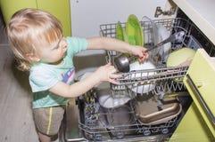 Entzückender lächelnder blonder Kleinkindjunge, der in der Küche nimmt Platten aus Geschirrspülmaschine heraus hilft Stockfoto