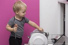 Entzückender lächelnder blonder Kleinkindjunge, der in der Küche nimmt Platten aus Geschirrspülmaschine heraus hilft Stockbilder