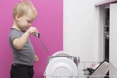 Entzückender lächelnder blonder Kleinkindjunge, der in der Küche nimmt Platten aus Geschirrspülmaschine heraus hilft Stockfotografie