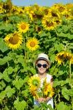 Entzückender lachender blonder Junge in den Sonnenbrillen und im Hut mit Sonnenblume auf Feld draußen Stockfoto