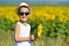 Entzückender lachender blonder Junge in den Sonnenbrillen und im Hut mit Sonnenblume auf Feld draußen Lizenzfreie Stockfotografie
