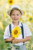 Entzückender lachender blonder Junge im Hut mit Sonnenblume auf Feld draußen Stockfotografie