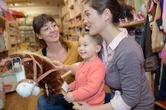 Entzückender Mädchenblick zu den Spielwaren am Spielzeugsladen mit Mutter lizenzfreie stockfotos