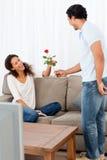 Entzückender Mann, der seiner Freundin eine Rose gibt lizenzfreies stockbild