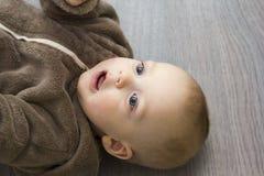 Entzückender 9-monatiger Junge im braunen Pelzkapuzenpulli legt auf den grauen Boden Stockfotografie