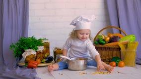 Entzückender netter Mädchenchef, der gesundes Lebensmittel unter Verwendung des Gemüses und der Wanne kocht stock video footage