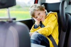 Entzückender netter Vorschulkinderjunge, der im Auto im gelben Regenmantel sitzt lizenzfreies stockbild