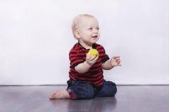 Entzückender Säuglingsjunge, der auf dem grauen Boden mit Apfel sitzt Stockfotografie