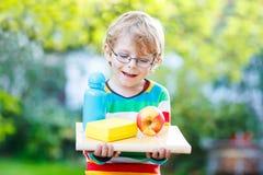 Entzückender Schuljunge mit Buch-, Apfel- und Getränkflasche Stockbild