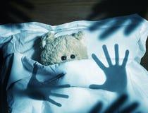 Entzückender Teddybär, der in das Bett, erschrocken legt Lizenzfreie Stockbilder