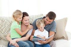 Entzückender Vater und Sohn, die ein Buch liest lizenzfreie stockfotografie