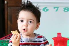Entzückender Vorschüler, der Cracker isst stockfoto