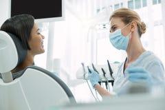 Entzückender Zahnarzt, der ihren Patienten betrachtet Stockfotos