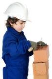 Entzückender zukünftiger Erbauer, der eine Backsteinmauer konstruiert Stockbild