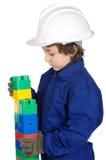 Entzückender zukünftiger Erbauer, der eine Backsteinmauer mit Spielzeugstück konstruiert Stockfoto