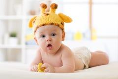 Entzückendes Baby, das auf Bauch und weared lustigem Giraffenhut liegt stockfotografie