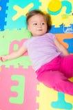 Entzückendes Baby, das auf Bodenmatten liegt Lizenzfreie Stockbilder
