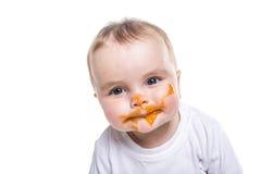 Entzückendes Baby, das eine Verwirrung bei der Fütterung macht lizenzfreies stockbild