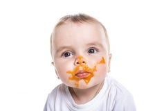 Entzückendes Baby, das eine Verwirrung bei der Fütterung macht lizenzfreie stockbilder