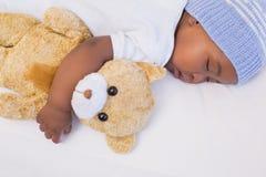 Entzückendes Baby, das friedlich mit Teddybären schläft Lizenzfreie Stockfotografie