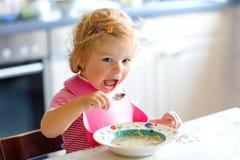 Entzückendes Baby, das Löffelvon der gemüsenudelsuppe isst Lebensmittel-, Kinder-, Fütterungs- und Entwicklungskonzept Nettes Kle lizenzfreies stockbild