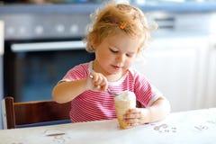 Entzückendes Baby, das von der süßen Eiscreme des Löffels im Waffelkegel isst Lebensmittel-, Kinder-, Fütterungs- und Entwicklung stockfoto