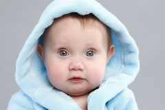 Entzückendes Baby in einem blauen Bademantel Stockbilder