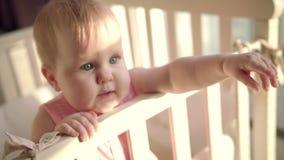 Entzückendes Baby erreichen heraus Hand im Feldbett Kleines Kind mit interessantem Gesicht stock video