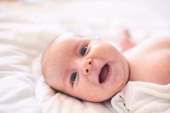 Entzückendes Baby im weißen sonnigen Schlafzimmer Neugeborenes Kinderkind, das im Bett sich entspannt stockfotografie