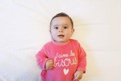 Entzückendes Baby kleidete in der rosa Kleidung an, die oben schaut Stockfotografie