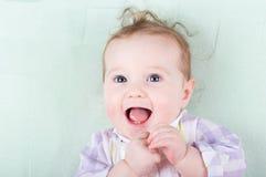 Entzückendes Baby mit dem lustigen gelockten Haar glücklich lachend Lizenzfreie Stockfotos