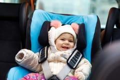 Entzückendes Baby mit den blauen Augen, die im Autositz sitzen Kleinkindkind im Winter kleidet das Gehen auf Familienurlaube und Stockfoto
