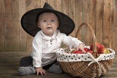 Entzückendes Baby mit Halloween-Hut und -äpfeln Stockbilder