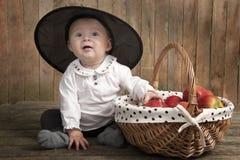 Entzückendes Baby mit Halloween-Hut und -äpfeln Stockfoto