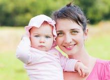 Entzückendes Baby mit ihrer Mutter Stockbild