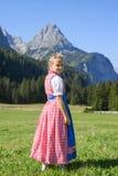 Entzückendes bayerisches Mädchen in einer schönen Berglandschaft Stockfotos